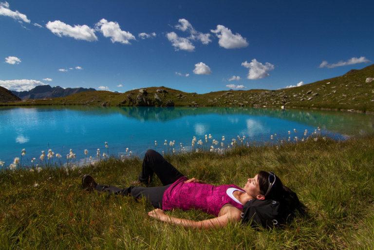 Frau liegt entspannt am Bergsee